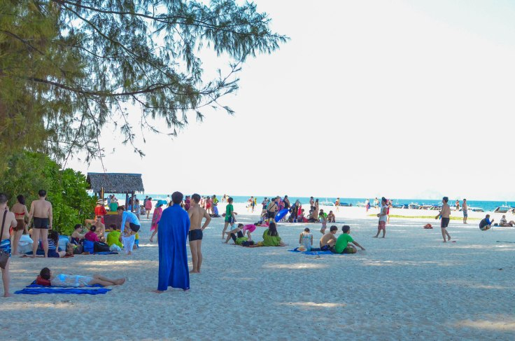 Beachgoers lounging and walking about